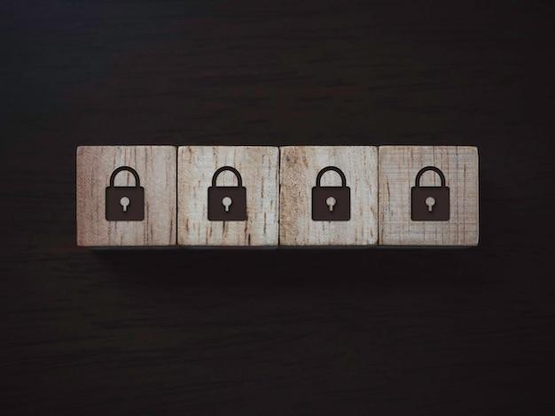 Privacy en bescherming van persoonsgegevens concept. vier slotpictogram op houten blokken op donkere houten achtergrond, bovenaanzicht. wachtwoord beveiliging.