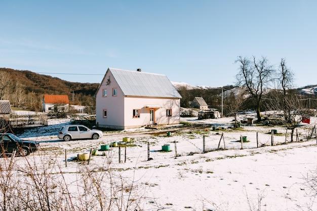 Privé accommodatie in een heuvelachtig gebied in de winter op sneeuw met geparkeerde auto's