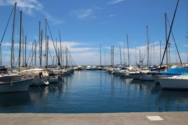 Prive-boten geparkeerd in de haven onder de zuivere blauwe lucht