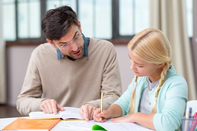 Privé-leraar en meisje die thuis nieuwe informatie schrijven