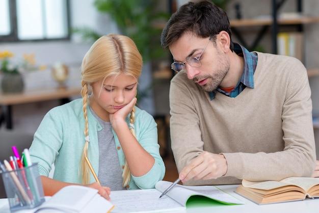 Privé-leraar en meisje thuis vooraanzicht