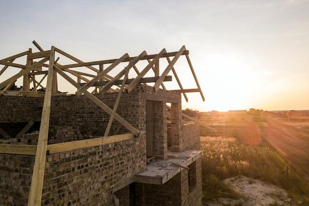 Prive-woning met houten dak frame structuur in aanbouw. onvoltooide bakstenen gebouw in ontwikkeling.