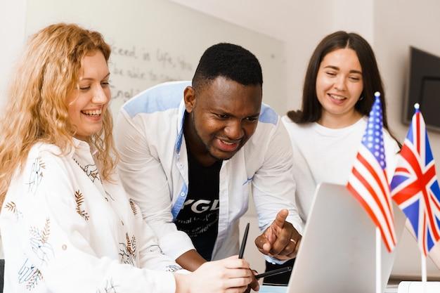 Privéstudie op buitenlandse school met een schoolmeisje. leraar legt grammatica van moedertaal uit met behulp van laptop
