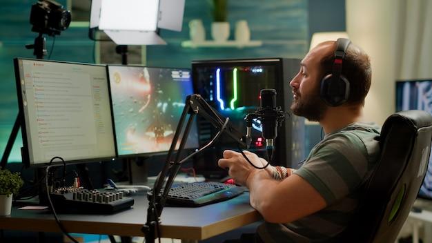 Pro cyberstreamer verliest videogametoernooi terwijl hij een professionele headset draagt met een draadloze controller. versloeg gamer met joystick voor online competitie 's avonds laat in de speelkamer