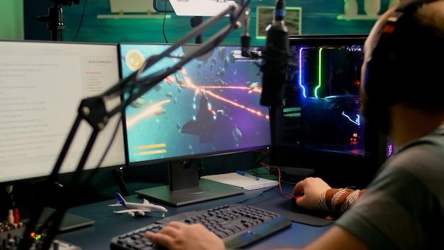 Pro-gamer die space shooter online videogames speelt met rgb-toetsenbord en muis tijdens virtueel kampioenschap