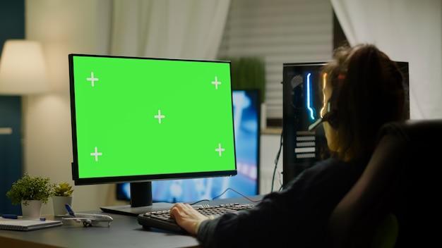 Pro-gamer die virtuele videogame speelt op krachtige computer met groen scherm mock-up, chroma key-display. cyberspeler die professionele pc gebruikt met geïsoleerde desktop-streaming-shooter-games met headse