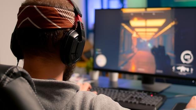 Pro-gamer speelt op krachtige computer first person shooter-videogame tijdens live kampioenschap, met een koptelefoon op. competitief spelerstreaming-videogametoernooi met professionele apparatuur