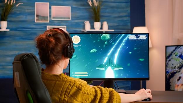 Pro-gamer zet headset op en test nieuwe space shooter-videogame die thuis op professionele computer wordt gespeeld
