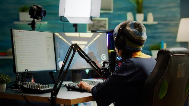 Pro-streamer controleert geluid op mixer die headset opzet en begint fps-videogame te spelen tijdens virtuele competitie. gamer die professionele streaming-instellingen gebruikt, chat streamen in gaming-thuisstudio