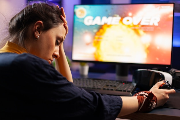 Pro-videogames die het hoofd bij de hand houden na het verliezen van een ruimteschietspel met een draadloze joystick. verslagen gamer die vr-hoofdtelefoon draagt voor online kampioenschap die 's avonds laat op een gamestoel zit