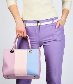 Probeer iets anders. winkelen en zaken doen. meisje met vluchtkoppeling. draag een elegante stijl. mannequin houdt leren tas vast. vrouw in paarse broek. zakenvrouw in stijlvolle outfit.