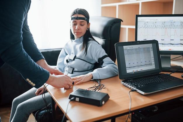 Probeer je geen zorgen te maken. meisje passeert leugendetector in het kantoor. vragen stellen. polygraaftest