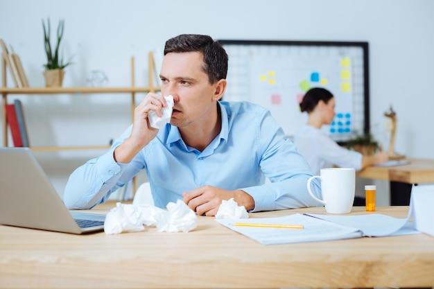 Probeer je te concentreren. knappe mannelijke persoon blauw shirt dragen en armen leunend op de tafel terwijl zijwaarts kijken