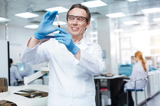 Probeer serieus te zijn. knappe mannelijke persoon die beschermende bril draagt en glimlach op zijn gezicht houdt tijdens het testen van bloed