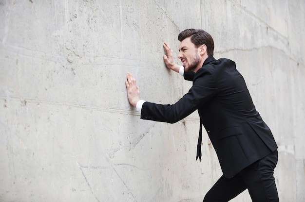 Probeer uit de stress te komen. gefrustreerde jonge man in formele kleding die tegen de muur duwt terwijl hij buiten staat