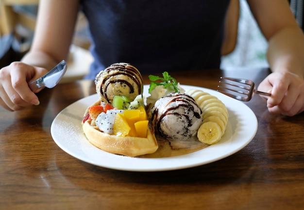 Probeert vork en mes te gebruiken om wafels te eten, geserveerd met gemengd fruit, in plakjes gesneden banaan
