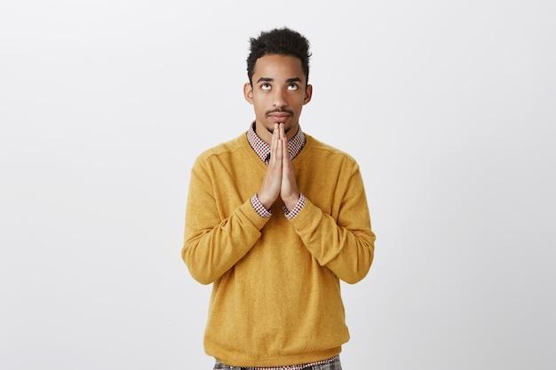 Proberen contact te maken met god door te bidden. gerichte knappe afrikaanse sportman met afro-kapsel die de handpalmen bij elkaar houdt en omhoog kijkt, gefocust terwijl hij de veiligheid van het gezin wenst of hoopt