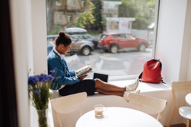 Proberen te studeren. vriendelijke mannelijke persoon die benen kruist terwijl hij op een groot raam zit