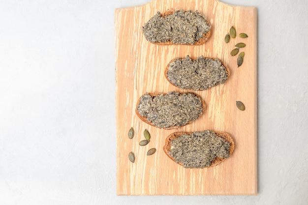 Probiotisch gekweekte veganistische kaaspasta gemaakt van pompoenpitten verspreid over sneetjes brood bovenaanzicht ...
