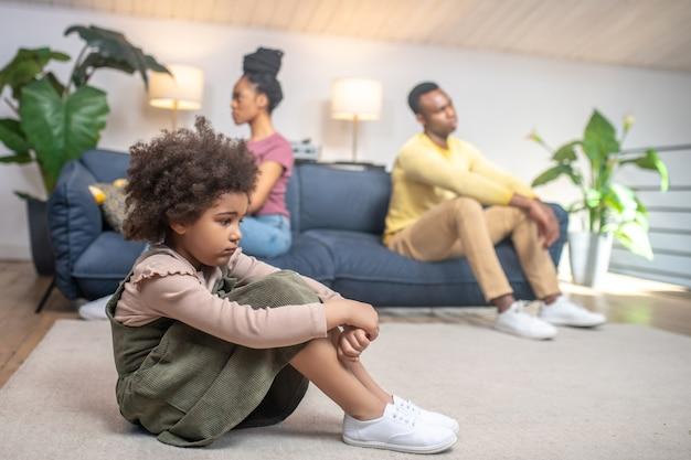 Probleem, familie. profiel van een triest dochtertje met een donkere huid dat op de grond zit en ongelukkige ouders die zich van elkaar afwenden op de bank