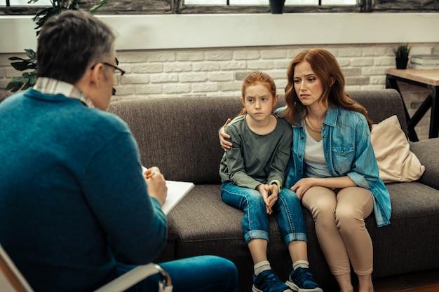 Probleem in communicatie. aardige trieste vrouw die haar dochter knuffelt terwijl ze samen een psycholoog bezoekt