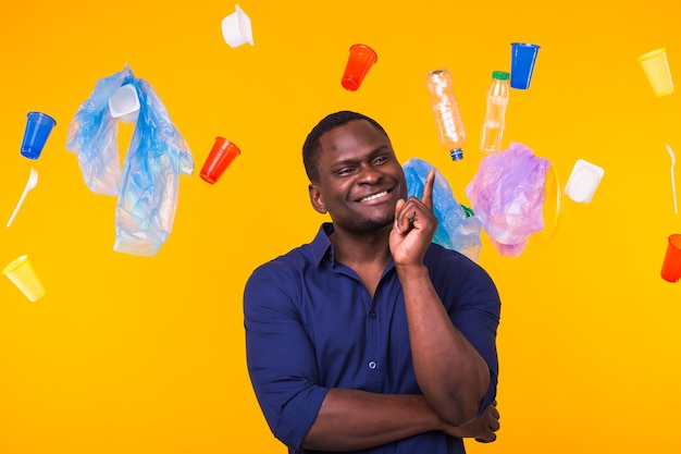 Probleem van afval, plastic recycling, vervuiling en milieuconcept - ernstige afro-amerikaanse man die op afval op gele muur kijkt. hij denkt aan ecologie.