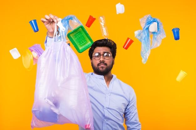 Probleem van afval, plastic recycling, vervuiling en milieuconcept - man met vuilniszak op gele muur.