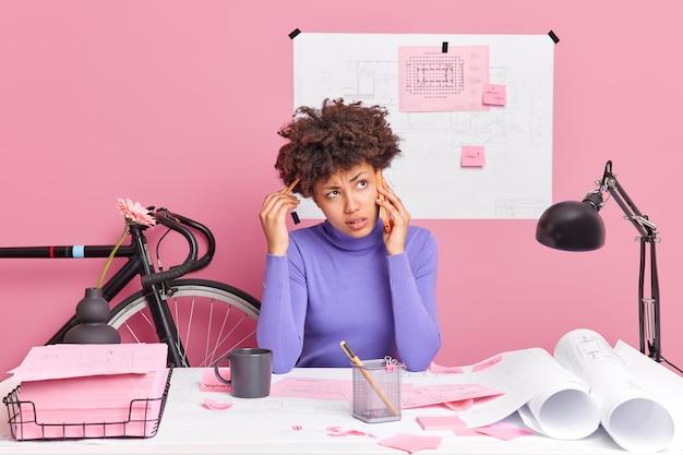 Probleemoplossend concept. verbaasde afro-amerikaanse vrouw heeft telefoongesprek en probeert te beslissen hoe ze beter haar hoofd kan krabben met pensilhoudingen op desktoppapieren in de buurt. baanbezettingsconcept