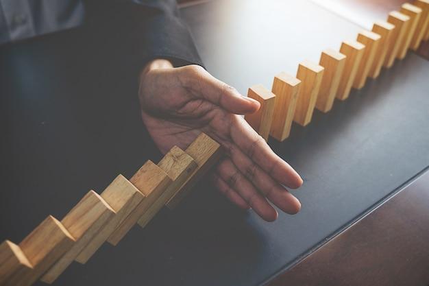 Probleemoplossing, close-up zicht op de hand van zakenvrouw stoppen met vallende blokken op tafel voor concept over het nemen van verantwoordelijkheid.