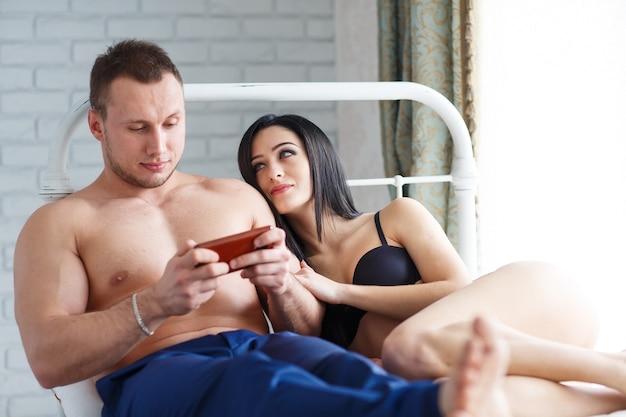 Problemen in het gezin. boze jonge vrouw die op het bed ligt, tegen haar echtgenoot, die het spel aan de telefoon speelt.