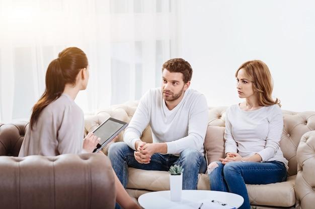 Problemen in relatie. ongezellig leuk jong stel zittend op de bank en kijken naar de psycholoog terwijl ze hun problemen bespreken