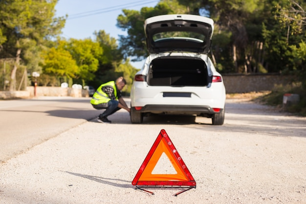 Problemen met de auto op de weg moeten een noodbord plaatsen
