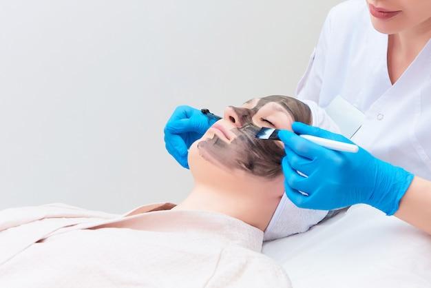 Procedure carbon gezichtspeeling in de kliniek van laserkosmetiek.