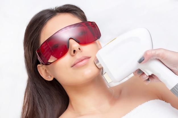 Procedure van foto-epilatie in de schoonheidssalon. jonge vrouw die epilation-laserbehandeling op gezicht ontvangen op schoonheidscentrum dicht omhoog