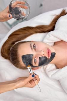 Procedure voor het aanbrengen van een zwart masker op de frisse huid van het gezicht van een mooie vrouw, bovenaanzicht. spa-behandelingen, huidverzorging, beauty concept. aantrekkelijke vrouwelijke blik op camera, close-up foto. kopieer ruimte