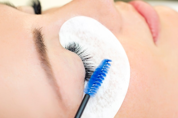 Procedure voor wimperverlenging. mooie vrouw met lange wimpers in een schoonheidssalon. wimpers close-up. borstel in de handen