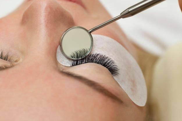 Procedure voor wimperverlenging. mooie vrouw met lange wimpers in een schoonheidssalon. wimpers close-up. een spiegel in de handen van een meester