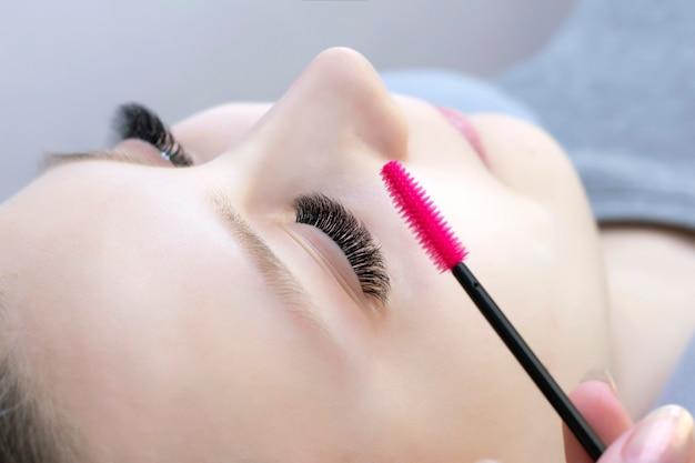 Procedure voor wimperverlenging. mooie vrouw met lange wimpers in een schoonheidssalon. wimpers close-up. penseel in de handen van de meester