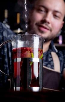 Proces het brouwen van thee, theeceremonie. barman giet heet water in de ketel om bessenthee te zetten.
