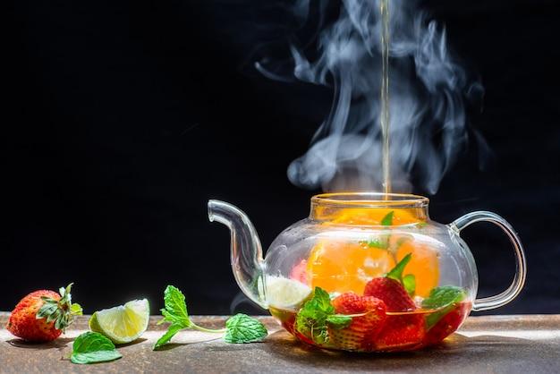 Proces het zetten van thee, donkere stemming. de stoom van hete thee wordt uit de ketel gegoten in een ketel met theeblaadjes, rode bessen, aardbeien, mandarijn, citroen, munt