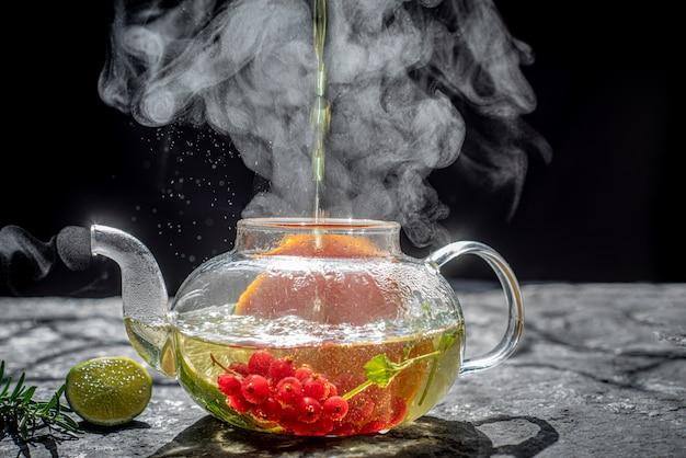 Proces het zetten van thee, donkere stemming. de stoom van hete thee wordt uit de ketel gegoten in een ketel met theeblaadjes, rode bessen, mandarijn, citroen, rozemarijn, munt