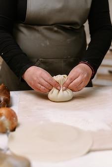 Proces koken. vrouw die khinkali voor zijn familieclose-up maakt. het voorbereiden van georgische traditionele maaltijd van deeg en vlees bij keuken. nationale keuken, kookproces concept