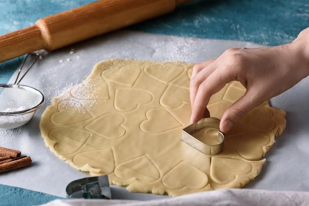 Proces om het hartvorm van het koekjesdeeg op blauwe keukenlijst, eigengemaakt koekjesconcept te maken