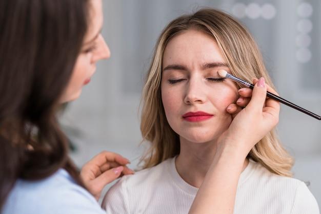 Proces om make-up aan blonde mooie vrouw te maken