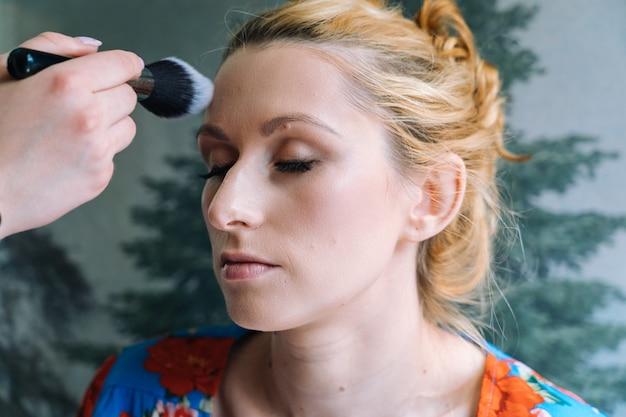Proces om make-up te maken. visagist aangebracht met penseel op model gezicht. portret van jonge gembervrouw in schoonheidssalon. hand van make-up master met kwast maakt perfecte huid en kleur oogschaduw
