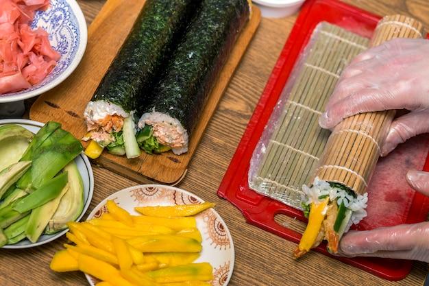 Proces om sushi en broodjes te maken. close-up van de handen van de mensenchef-kok die traditioneel japans voedsel thuis of in restaurant op keukenlijst voorbereiden.