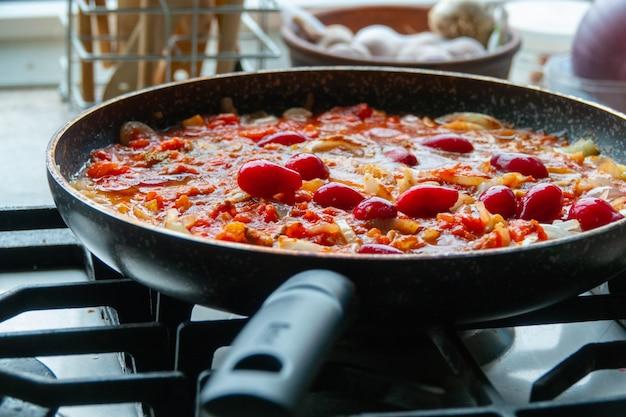 Proces om tomatensaus voor pasta in a door de ingrediënten te koken