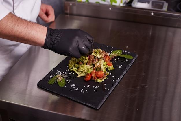 Proces om warme salade met kalfsvlees te koken. handen van een chef-kok in zwarte handschoenen. zwart leisteen bord.