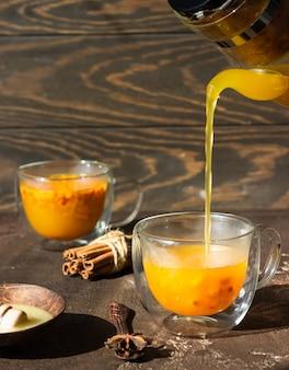 Proces thee zetten, hete kleurrijke duindoornthee wordt in een glazen beker gegoten