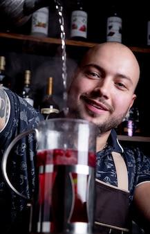Proces thee zetten, theeceremonie. barman giet heet water in de waterkoker om bessenthee te zetten
